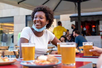 black woman with afro hairstyle sitting at a coffee table with beers and snacks, moment of optimism and happiness for the end of the lockdown