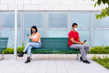 an attractive girl sitting on the bench looks at her mobile phone, at a distance of one meter a guy uses his mobile phone, concept of social distancing in times of outbreak