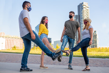 group of young friends with protective mask doing greetings with foots for preventing corona virus outbreak, physical distance and safety greetings concept, the new normal way of be social
