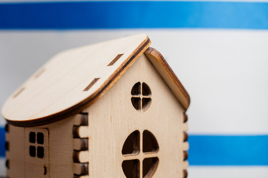 Small wooden house, Israel flag on background. Real estate concept, soft focus