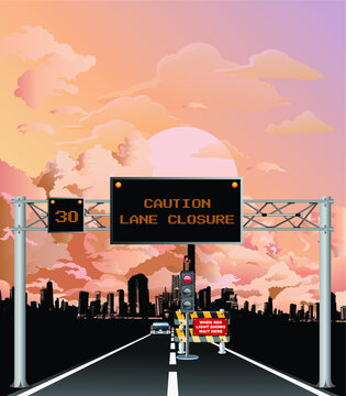 Roadway overhead digital gantry sign with caution roadworks lane closure message and temporary traffic lights set against a stunning dawn or dusk pink cloudy sky