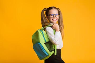 Schoolgirl Posing With School Backpack Smiling To Camera, Studio Shot