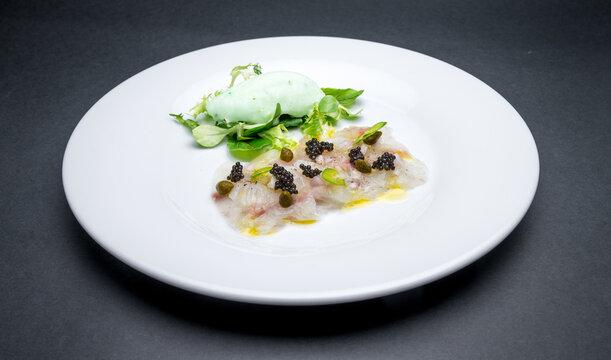 Fresh fish carpaccio with black sturgeon caviar