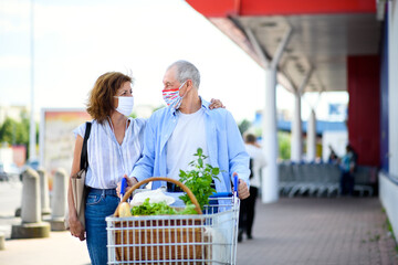 Senior couple with face masks and shopping walking outside supermarket in city.