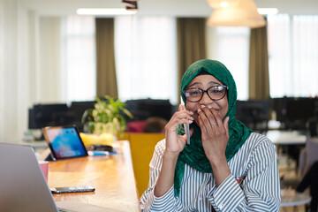 african muslim business woman using mobile phone