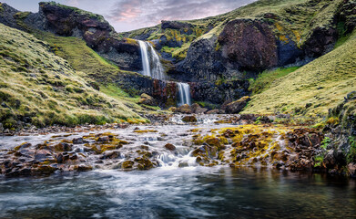Typical Icelandic scenery. Fresh green hills and waterfall. Picture of wild area. Iceland. Amazing nature landscape. long exposure image. Picture of wild area. Most beautyful locations in world