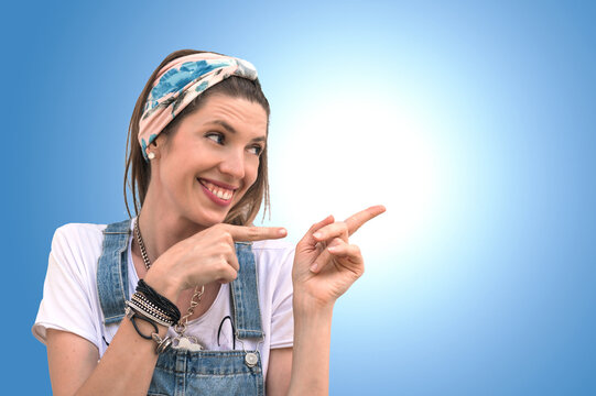 Portrait of a young woman pointing fingers to the left on blue background. The girl smiles and points to the side. Copy space