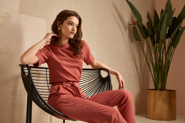Obraz Beautiful brunette woman natural makeup wear fashion clothes casual dress code office style total pink blouse and pants suit, romantic date business meeting armchair interior stairs flowerpot. - fototapety do salonu