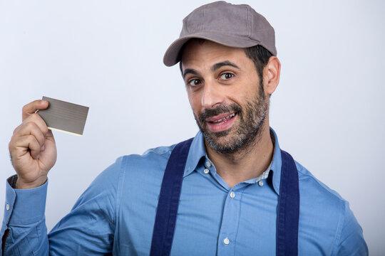 fattorino con cappellino camicia e blocco notes giallo in mano , mostra una tessera con l'altra mano, isolato su sfondo bianco