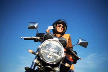 Motorcycle riding school and courses. Student with helmet and reflective vest riding motorcycle on...