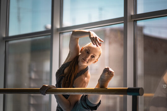 Young woman doing stretching on ballet barre.