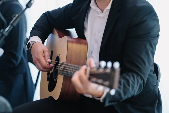 Closeup shot of a male in a suit playing the guitar during an event