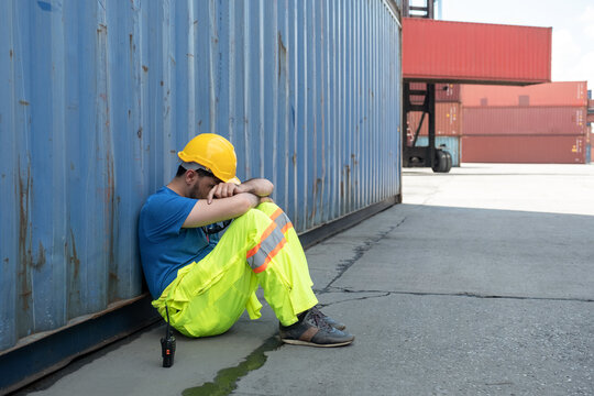 Depressed and tried foreman or worker sitting side container in ship yard logistic factory because losing his job or fired.
