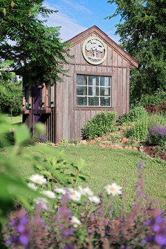 Old Wooden Cottage Style Shed near Flowers in a Country Garden
