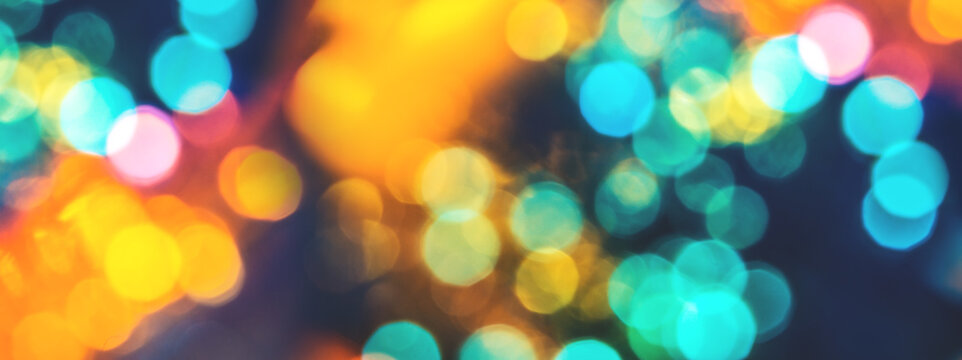 Colorful background with natural bokeh texture and defocused sparkling lights. Teal and orange blur with background with twinkling lights. Festive lights overlay or web banner with copy space