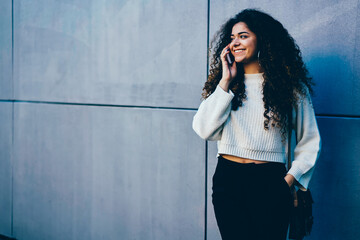 Positive teen woman dressed in trendy outfit talking on cellphone during leisure time at street.Cute smiling hipster girl enjoying recreation at urban setting with modern device and good mood