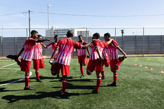 Multi ethnic team of male football players training at a sports field