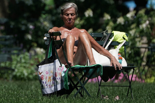 A woman closes her eyes as she soaks up the sun on the lawn at Bryant Park in the Manhattan borough of New York City
