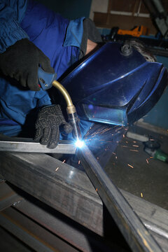 Electric arc welding. The worker welding two iron corners.