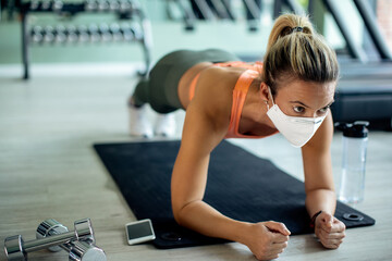 Athletic woman with face mask exercising in plank pose at the gym.