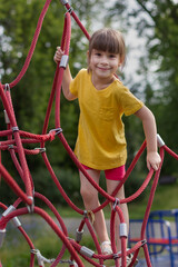 Poster de jardin Doux monstres Adorable 6 years old girl climbing the net in the playground