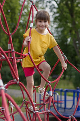 Photo sur Plexiglas Doux monstres Adorable 6 years old girl in the yellow t-shirt on the playground.