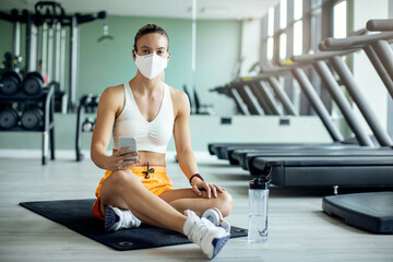 Sportswoman wearing protective face mask while using mobile phone in a gym.