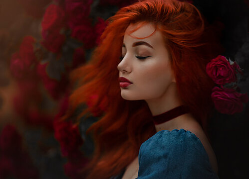 Portrait of a red haired girl in blue dress. Pretty young model between red roses, wind in the hair.Art work.