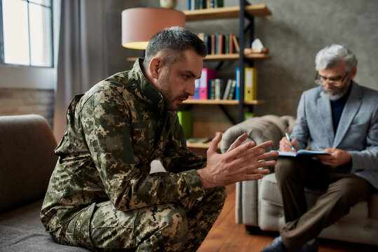 Regain. Thoughtful middle aged military man communicating with psychologist, sitting on the couch during therapy session. Soldier suffering from depression, psychological trauma. PTSD concept