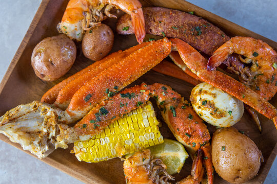 Platter of southern garlic crabs seafood boil with Alaskan crab legs, small new red potatoes, corn on the cob, and shrimp