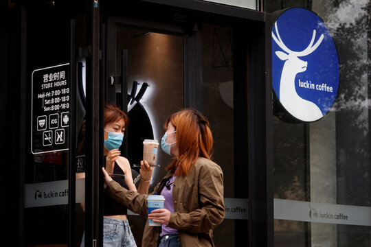 Women leave a store of the Chinese coffee house chain Luckin Coffee in Beijing