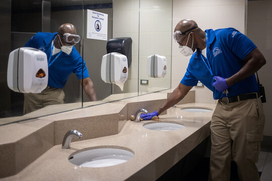 An airport custodian cleans a bathroom sink at IAH George Bush Intercontinental Airport in Houston
