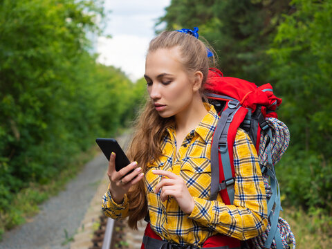 Hiker woman lost in forest. She using mobile GPS map.