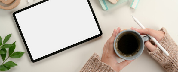 Female student hands holding coffee mug while working with mock up tablet on study table
