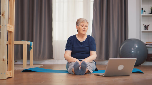 Senior woman sitting on yoga mat stretching boyd sitting on mat. Online learning and study, Active healthy lifestyle sporty old person training workout home wellness and indoor exercising