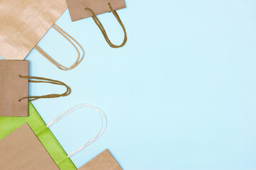 Kraft paper merchandise bag set on blue background. Copy space. Eco friendly packaging. Shopping, sale minimal concept