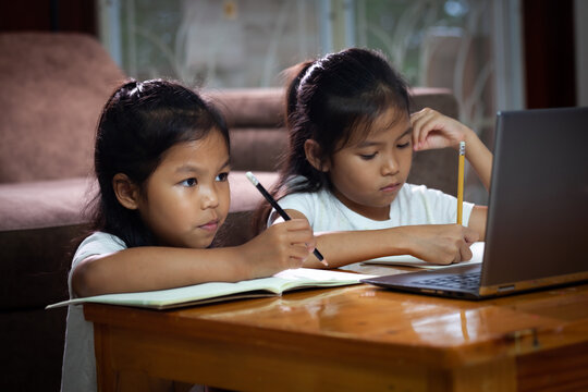 Two asian child girls using notebook to learning online technology with her sister together. Concept of online education, social distance learning at home during quarantine and school holidays.