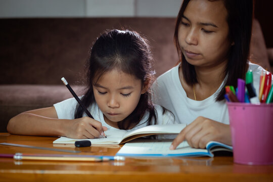 Young asian mother helping her daughter do her homework at home. Education from home concept.