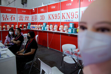 People wearing face masks are seen at a mask stall at a procurement fair for epidemic-prevention materials in Shanghai