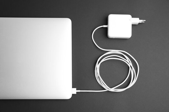 Laptop and charger on black background, flat lay. Modern technology