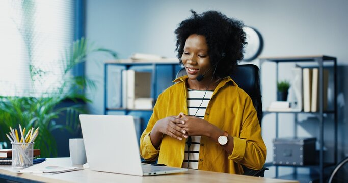 Pretty happy African American young woman sitting at office and talking on webcam on laptop in headset. Beautiful female worker having video call on computer at working place indoor. Job concept