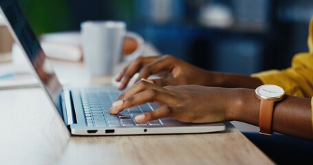 Close up shot of African American female hands typing on laptop while sitting at office desk indoors. Woman fingers tapping and texting on computer keyboard while working in cabinet. Work concept