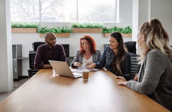 Diverse team of businesspeople meeting together around an office