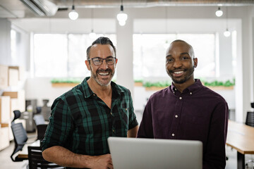 Diverse businessmen smiling and using a laptop in an office