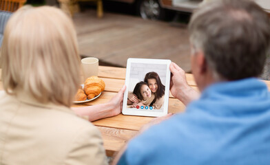 Senior couple communicating with their daughter and grandchild on tablet computer at campground