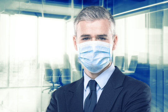 Businessman in suit wearing a face mask; office background