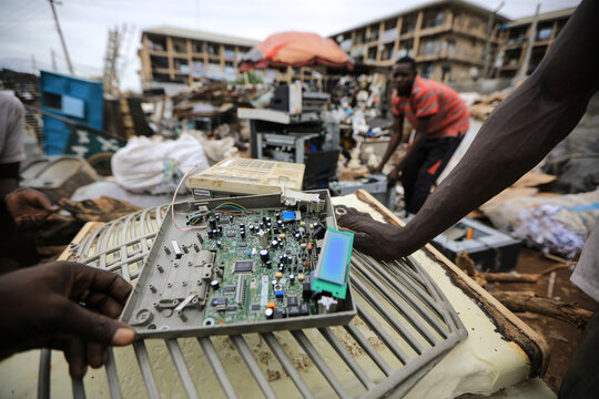 A man carries a discarded circuit board at a recycling centre in Abuja