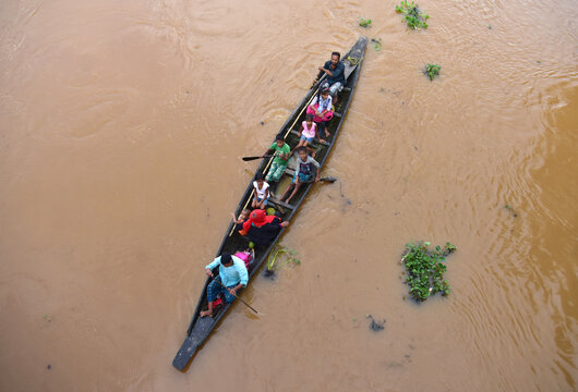 Flood-affected villagers are transported on a boat to a safer place at Kachua village