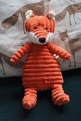 Obraz  Rudy lis, dziecięca zabawka na tle poduszki we wzory lisków - fototapety do salonu