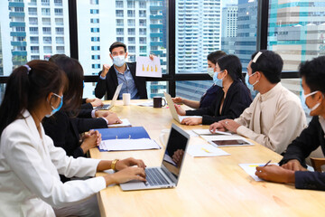 Executive team meeting during coronavirus or covid-19 for business new financial strategy after pandemic with all staff members wearing facial mask as of new normal and social distancing policy